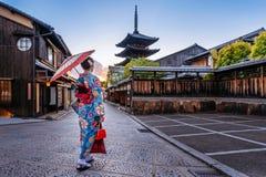 Mulher que veste o quimono tradicional japonês com o guarda-chuva no pagode de Yasaka e a rua de Sannen Zaka em Kyoto, Japão imagem de stock