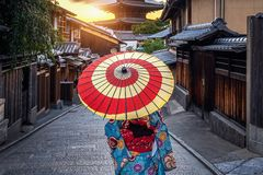 Mulher que veste o quimono tradicional japonês com o guarda-chuva no pagode de Yasaka e a rua de Sannen Zaka em Kyoto, Japão fotos de stock