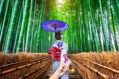 Mulher que veste o quimono tradicional japonês que guarda a mão do ` s do homem e que conduz o à floresta de bambu em Kyoto, Japã fotos de stock
