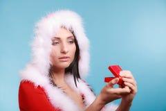 A mulher que veste o traje de Papai Noel guarda a caixa de presente no azul Imagem de Stock Royalty Free