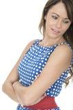 Mulher que veste os braços azuis de Dot Dress Looking Behind da polca dobrados foto de stock