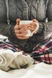 Mulher que veste os pyjamas acolhedores que sentam-se em uma cama com uma caneca de chá Imagem de Stock