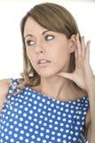 Mulher que veste a polca azul Dot Dress Eavesdropping Listening à conversação Imagem de Stock Royalty Free