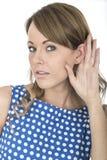 Mulher que veste a polca azul Dot Dress Eavesdropping Listening à conversação Imagem de Stock