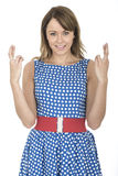Mulher que veste a polca azul Dot Dress Fingers Crossed Fotografia de Stock Royalty Free