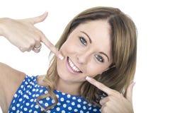 Mulher que veste a polca azul Dot Dress Pointing a seus dentes Fotografia de Stock Royalty Free