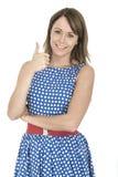 Mulher que veste a polca azul Dot Dress Thumbs Up Fotos de Stock Royalty Free
