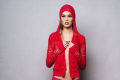 Mulher que veste a roupa vermelha no fundo cinzento fotografia de stock royalty free