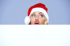 Mulher que veste Santa Claus Hat Peeking Over Edge fotografia de stock royalty free