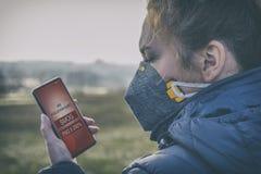 Mulher que veste uma máscara protetora contra a névoa real e que verifica a poluição do ar atual com o app esperto do telefone foto de stock royalty free