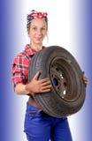 mulher que veste uma roda de carro do mecânico Fotografia de Stock