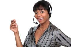 Mulher que veste uns auriculares do telefone Fotografia de Stock Royalty Free