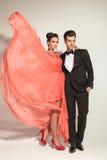 Mulher que vibra seu vestido coral ao abraçar seu amante Fotografia de Stock