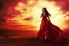 Mulher que voa o vestido vermelho, modelo de forma em levitar do vestido de noite imagem de stock