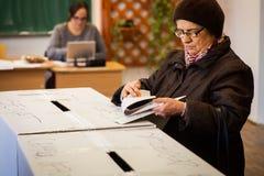 Mulher que vota na estação de votação Foto de Stock