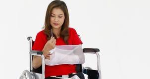 Mulher quebrada do braço na cadeira de rodas filme