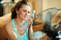 Mulher quente com a garrafa da água fria usando o fã metálico elétrico imagens de stock