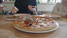 A mulher quer tomar a fatia de pizza quente no restaurante Fam?lia que come a pizza italiana real e que tem o divertimento Estilo vídeos de arquivo