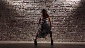 A mulher rítmica nos saltos altos dança o twerk contra uma parede de tijolo Movimento lento video estoque
