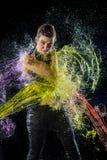 A mulher à rapaz na água colorida espirra Fotografia de Stock
