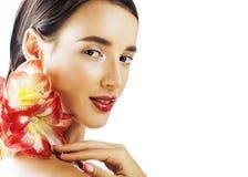 Mulher real moreno bonita nova com fim vermelho da amarílis da flor imagem de stock