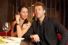 A mulher realiza em sua mão uma flor e flertar com homem Fotografia de Stock Royalty Free