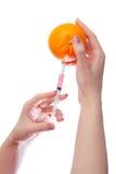 A mulher realiza no suringe e em laranjas médicos das mãos Imagem de Stock