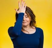 A mulher realiza o erro, pesares, golpeando a mão na cabeça para dizer duh Imagem de Stock