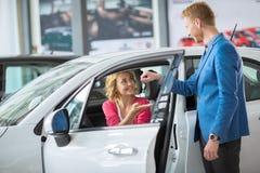 A mulher recebe as chaves a um carro novo de um gerente de vendas Fotografia de Stock Royalty Free
