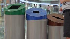 A mulher recicla o papel no balde do lixo com sinal do papel, do plástico e o de vidro Classifica??o e reciclagem Waste video estoque