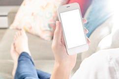 A mulher reclinou no sofá que guarda Smartphone Foto de Stock Royalty Free