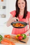 Mulher red-haired bem parecida que cozinha vegetais Imagens de Stock