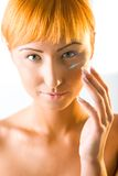 A mulher red-haired nova põr o creme sobre a face fotografia de stock