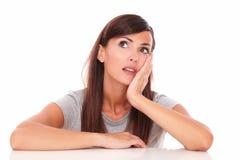 Mulher reflexiva que quer saber ao olhar acima Imagem de Stock