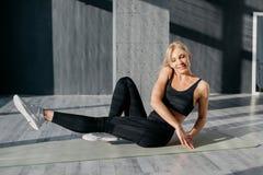 A mulher reforça os músculos da imprensa com carga dos exercícios foto de stock