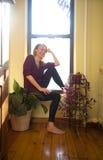 A mulher relaxa em casa imagem de stock royalty free