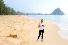 A mulher relaxa a manhã com o cão na praia Imagens de Stock Royalty Free