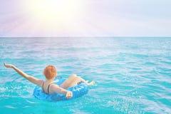 A mulher relaxa no anel inflável na água do mar fotos de stock royalty free