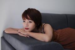 A mulher relaxa no sofá imagem de stock