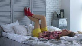 Mulher relaxado despreocupada que encontra-se na cama com os pés levantados filme