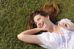 Mulher relaxado feliz que encontra-se na grama foto de stock