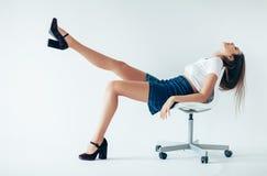 Mulher relaxado feliz que senta-se na cadeira com pé acima foto de stock
