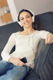 Mulher relaxado que escuta a música no sofá em casa Imagem de Stock