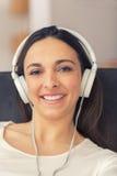 Mulher relaxado que escuta a música no sofá em casa Imagens de Stock
