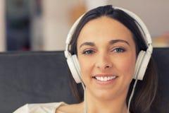 Mulher relaxado que escuta a música no sofá em casa Imagens de Stock Royalty Free