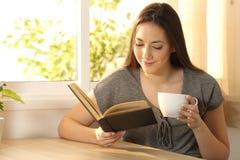 Mulher relaxado que lê um livro de papel Fotos de Stock Royalty Free