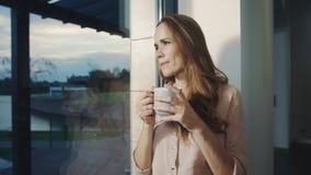 Mulher relaxado que sonha perto da janela após o dia de trabalho Consideravelmente mulher que tem o resto filme
