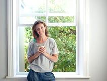 Mulher relaxado que sorri com a xícara de café pela janela em casa Imagem de Stock