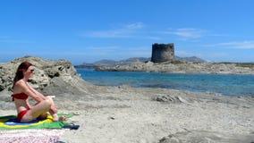 Mulher relaxado que toma o sol na praia de Pelosa, Sardinia, Itália Fotografia de Stock Royalty Free
