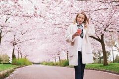 Mulher relaxado que toma uma caminhada na música de escuta do parque da mola Fotos de Stock Royalty Free